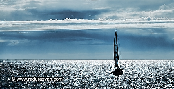 Silhouettes of a yacht sailing alone in the ocean to the horizon.