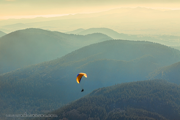 Paraglider flying over the volcanic mountains in the Central Massif, France in a beautiful autumn evening.