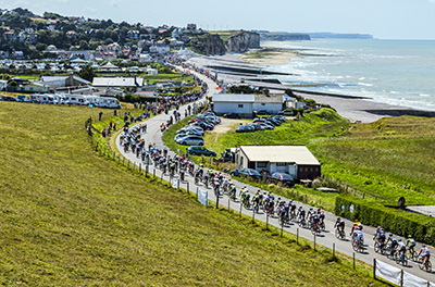 Sainte Marguerite sur Mer, France - 09 July 2015: The peloton riding near the beach in Normandy during the stage 6 of Le Tour de France .